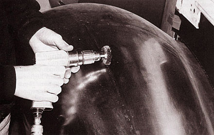 Removing paint by hand using a small wire-brush grinder