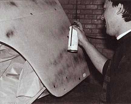 Restoration technician spraying primer onto body