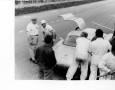 Hermann Lang, while refueling at Le Mans in 1952, gets out to see what the technicians are working on.