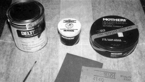 Paint supplies: can of paint, brush, sandpaper, wax