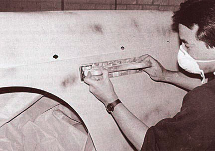 Restoration technician using a blocker to sand the dry surfacer